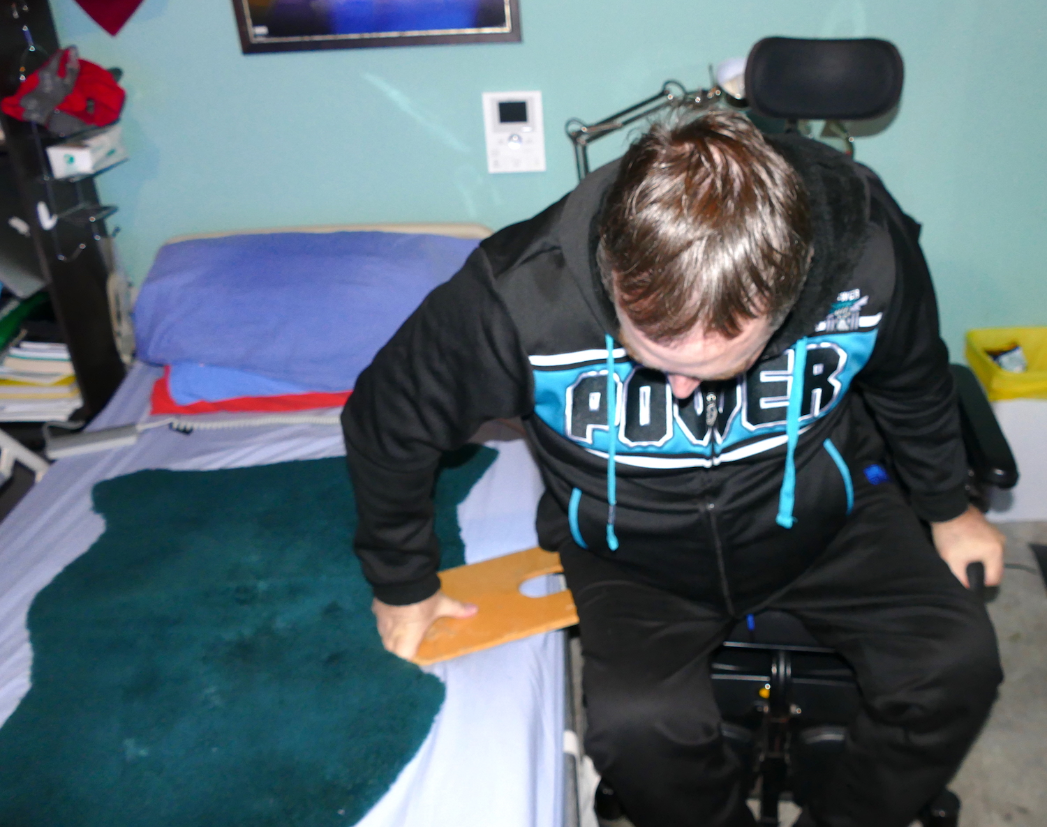 john getting onto bed from wheelchair usiing a slideboard - sci sleeping tips
