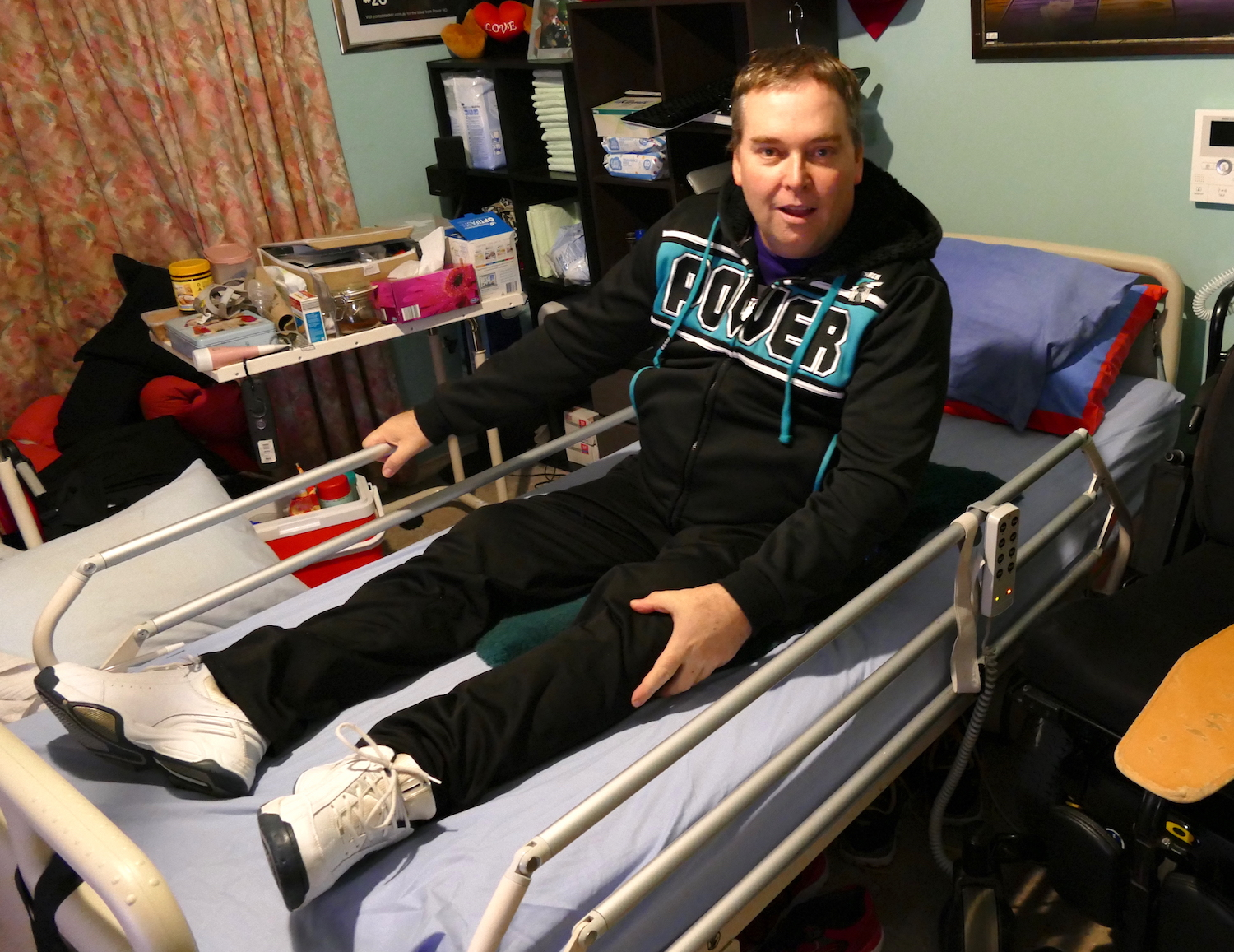 having safely arrived in bed, John pulls up the safety rail and smiles to the camera - sci sleeping tips