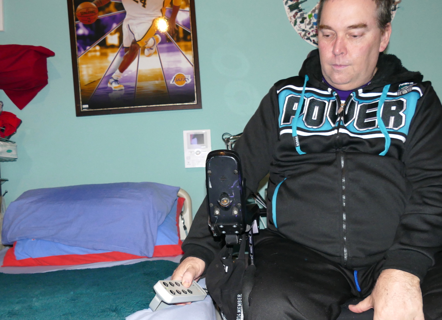 shows john in his powerchair adjusting height of bed - sci sleeping tips