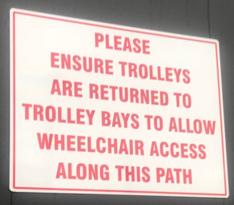 the sign reads 'please ensure trolleys are returned to trolley bays to allow wheelchair access along this path