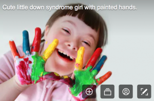 disability stock photographs - young girl with down syndrome who has hands painted in mulit colours