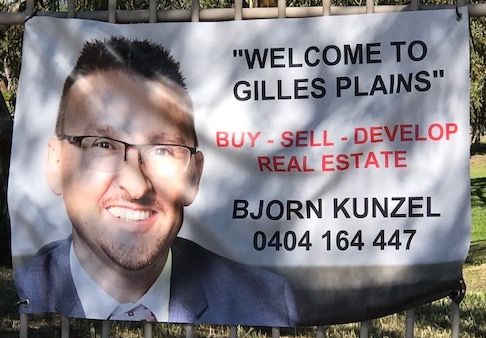 the huge face of the real estate salesmen from Weeks & Macklin Real Estate