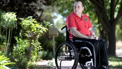 Wheelchair Blog - john sitting outside his house looking over his shoulder