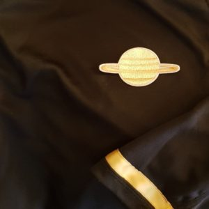 close up of a uniform on the Galactic Trek star ship. its brown and the symbol is Saturn.