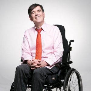 tim with a big smile sitting in wheelchair, and a pale business shirt and a red tie, fingers crossed. Adelaide Fringe Accessibility