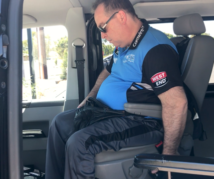 In my van, I am wearing a blue shirt and my left arm is reaching for the control which allows the seat to go up and down, rotate, and move backwards and forwards