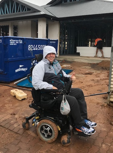 I am smiling and on my mud coated wheelchair, as I was stuck in the mud