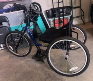 a blue framed 3 wheeled bike in a disorganised garage. The seat is the same height as a wheelchair. There are places to strap in feet, and the chair is totally controlled and pushed by hands. Council wheelchair accessibility is important for bikes too!