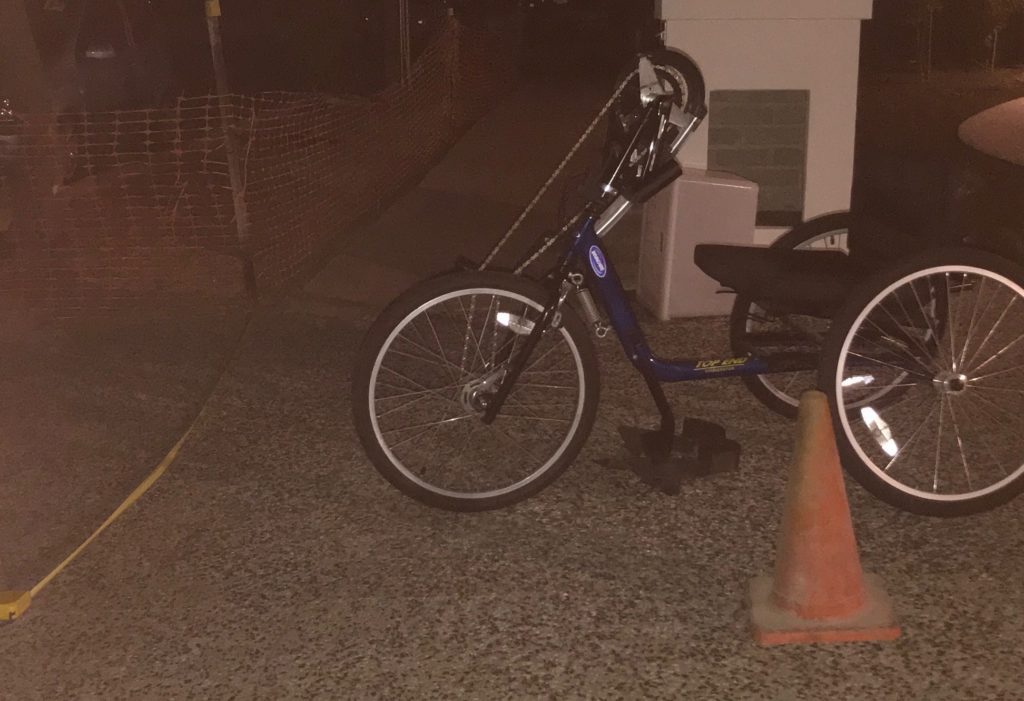 The bike is in the middle and is blue. A letter box and front verge is in the background. A traffic cone and tape measure is located near the bike