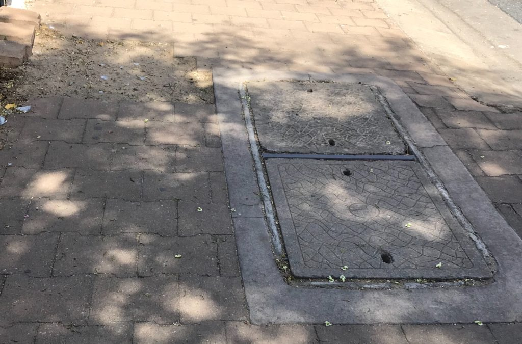 A pavement on a busy road/ 1/3 of the walkway is dirt and sand, the middle section is a utility hole with a cover, and the third part are pavers