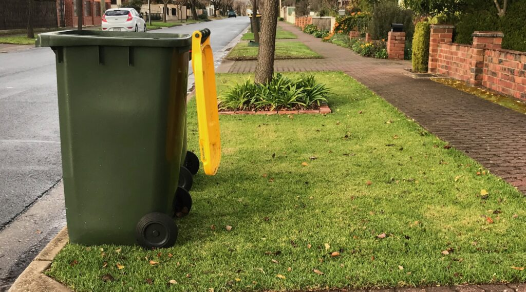 to the left is the council recycle bin with the typical yellow lid. It is next to the kerb and sitting on grass. Lid is open as it has been emptied