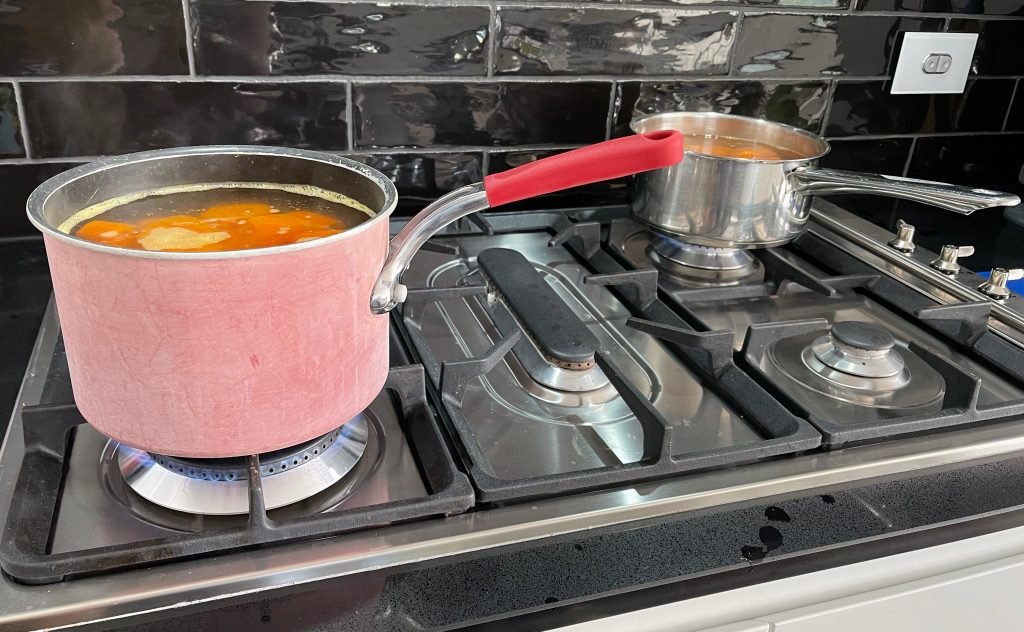2 pots on a gas stove are boiling water, and the carrots are being cooked. freezing carrots cooking