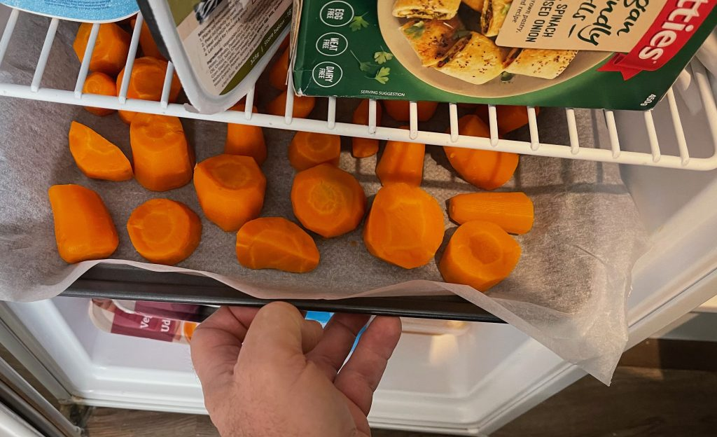 a freezer door is open, and a baking tray, has baking paper on it, and the pieces of carrot - freezing carrots cooking