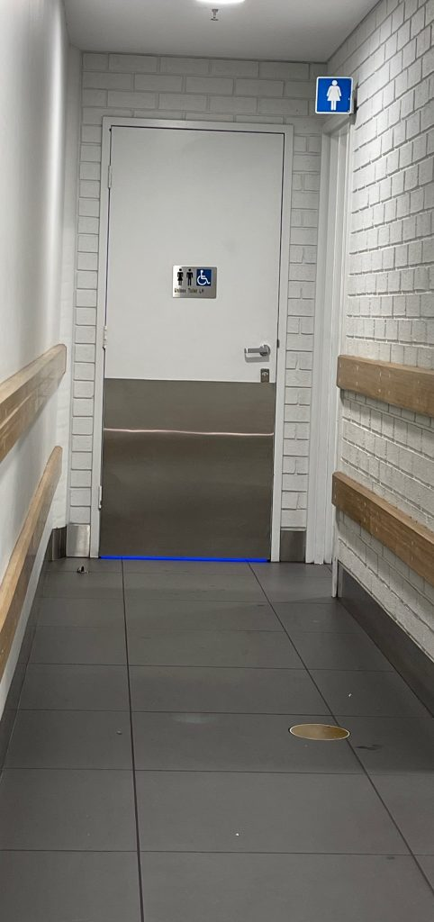 a corridor leads to the accessible toilet, blue light coming under the door, door is adjacent to the womens toilet