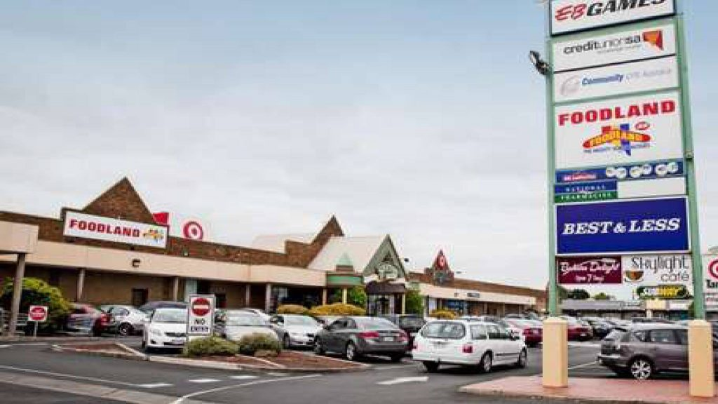 a large sign showing a few of the shops in the centre, a car park behind it with about 30 cars in it, and further back is the shopping centre - Sefton Plaza Accessibility