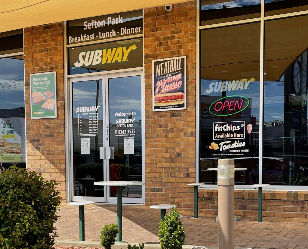 empty tables and chairs are outside subway, a double glass door on the left, and a window to the right