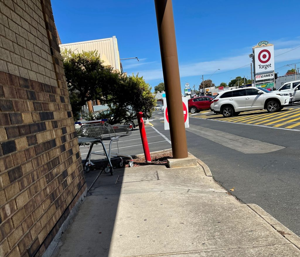 left is the wall of a shop, and to the right is the carpark. Around the shop is a concrete path, and a step exit from footpath to the car park. sefton plaza accessibility
