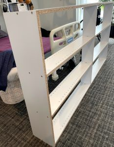 the bookshelf is against the bed