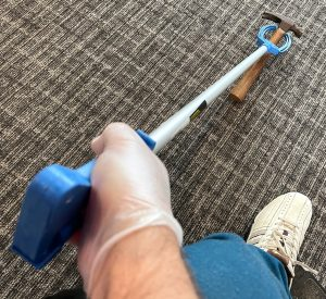 blue pickup stick is held and about to pick up a hammer